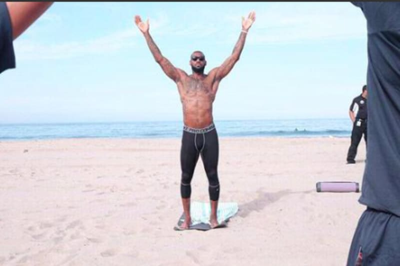Lebron James practicing yoga on a brach