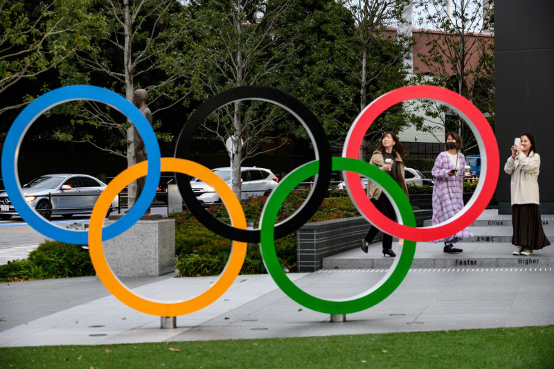 People take pictures of the Olympic Rings outside the closed Japan Olympic Museum in Tokyo on March 27, 2020, three days after the historic decision to postpone the 2020 Tokyo Olympic Games. (Photo by Philip FONG / AFP) (Photo by PHILIP FONG/AFP via Getty Images)